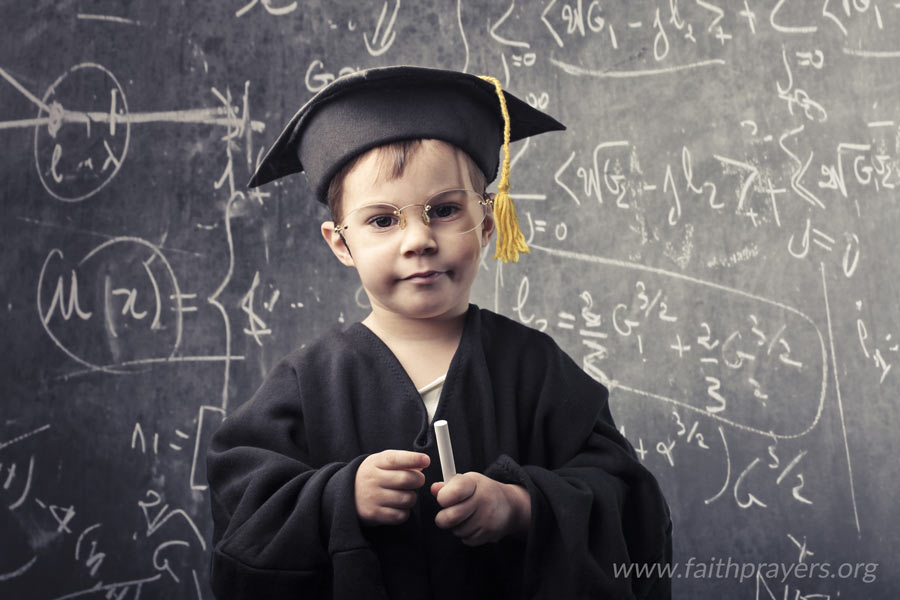 Child dressed in graduation gown standing in front of a blackboard while holding chalk